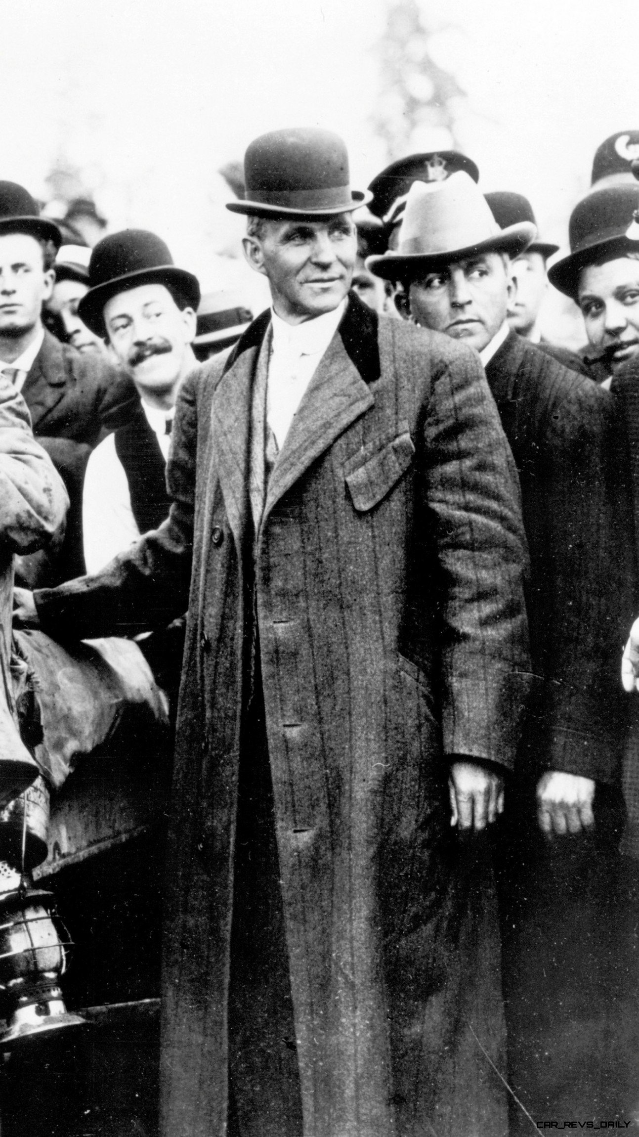 Henry Ford looking tough and handsome in long coat beside Rouge Assembly Plant -- ca ~1921