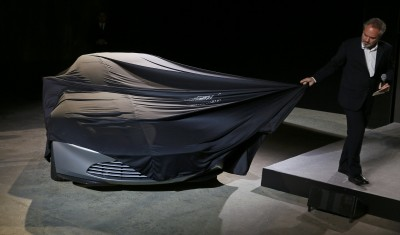 """Director Sam Mendes unveils an Aston Martin DB10 car during an event to mark the start of production for the new James Bond film """"Spectre"""" at Pinewood Studios"""